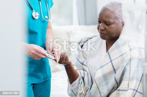 istock Home healthcare nurse checks patient's blood sugar 936497080