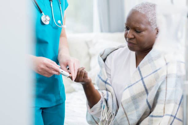 home healthcare nurse checks patient's blood sugar - diabetic stock photos and pictures