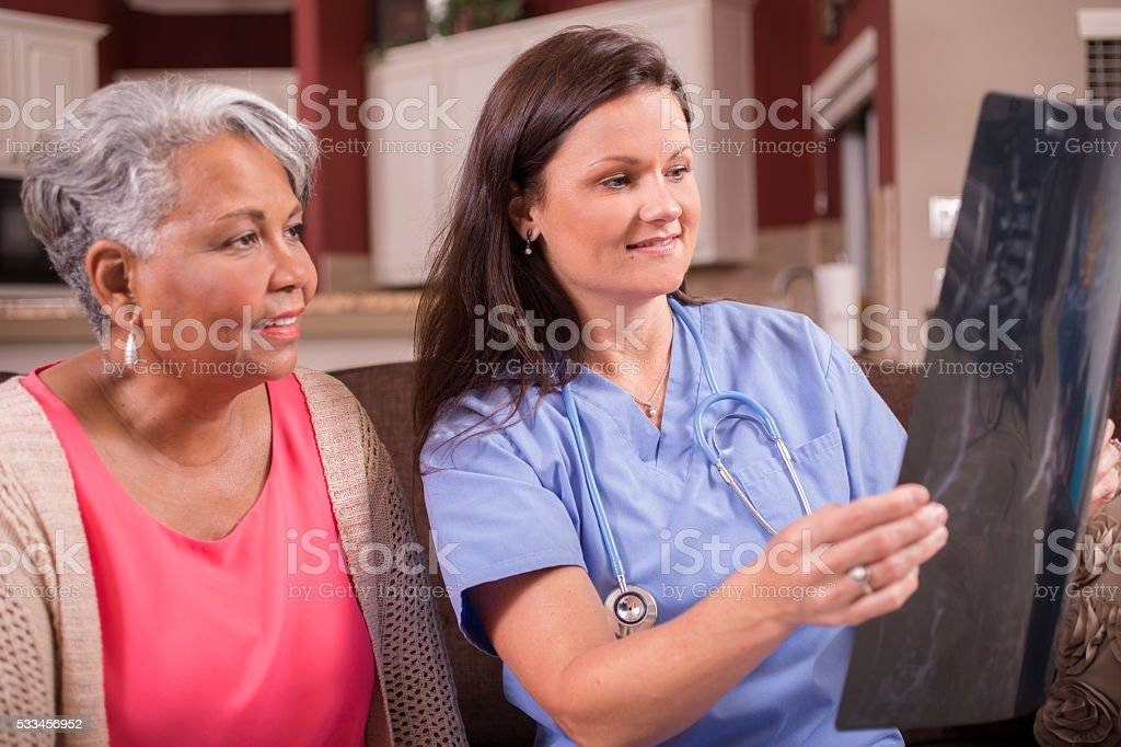 Home healthcare nurse discusses x-ray with senior adult woman. stock photo