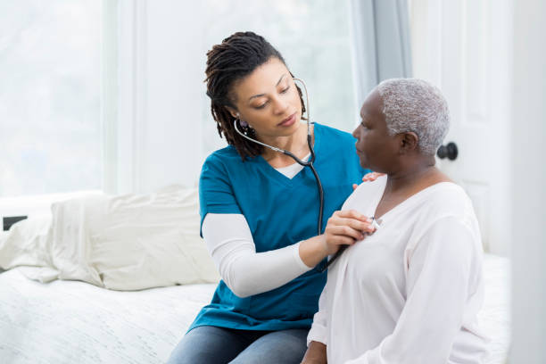Home healthcare nurse examines elderly patient Mid adult female nurse concentrates while listening to an elderly female patients heart and lungs during exam. lung stock pictures, royalty-free photos & images