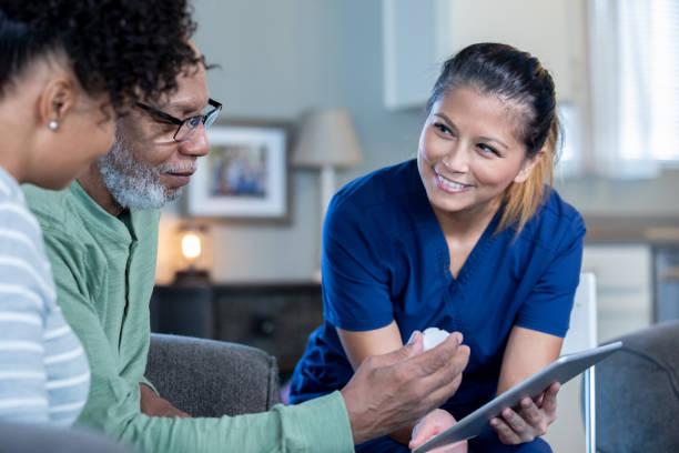 Home healthcare nurse explaining medication to senior man stock photo