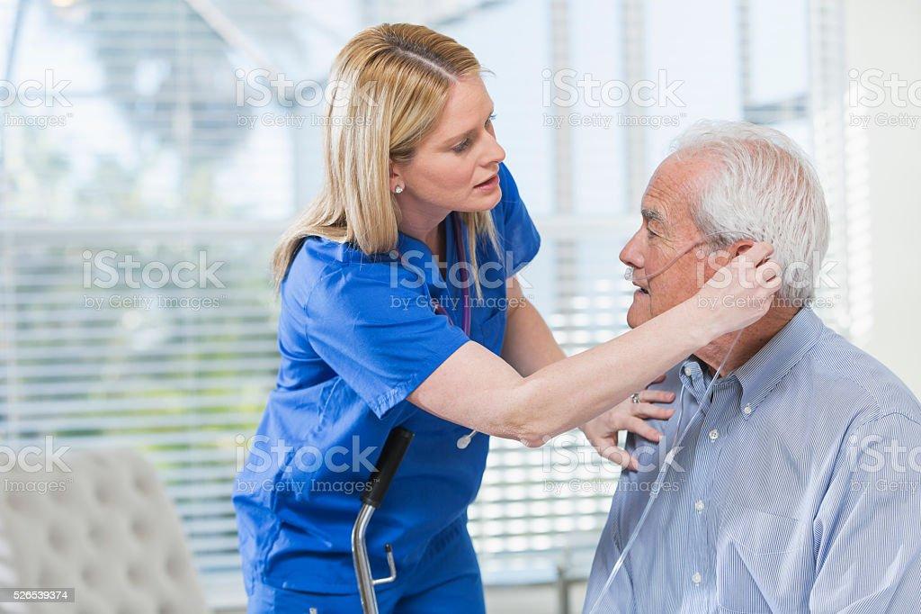 Home healthcare nurse helping elderly man with oxygen stock photo
