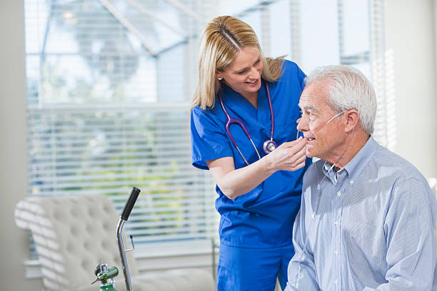Home healthcare nurse helping elderly man with oxygen Home healthcare worker helping a senior man with his portable oxygen tank. She is standing beside him in blue scrubs, adjusting the tubing. medical oxygen equipment stock pictures, royalty-free photos & images