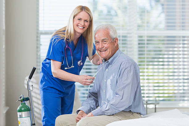 Home healthcare nurse helping elderly man with oxygen Home healthcare worker helping a senior man with his portable oxygen tank. The patient is sitting in his bedroom. The nurse is standing beside him in blue scrubs, adjusting the tubing. They are smiling and looking at the camera. medical oxygen equipment stock pictures, royalty-free photos & images