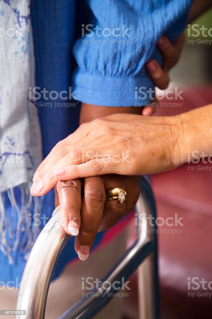 Home healthcare nurse helps senior woman use walker. stock photo