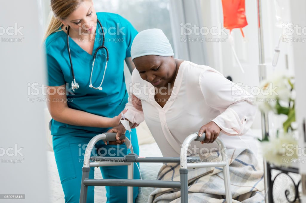 Home healthcare nurse helps woman get out of bed stock photo