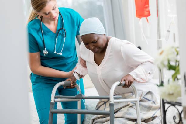 home gesundheit krankenschwester hilft frau aus dem bett - hospiz stock-fotos und bilder