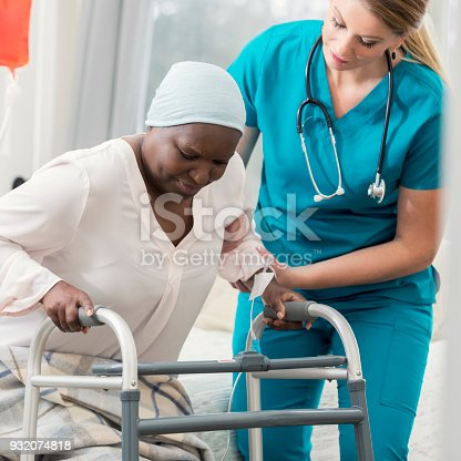 958891774istockphoto Home healthcare nurse helps woman stand up 932074818