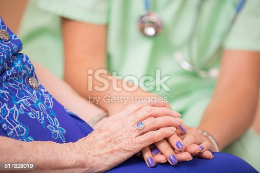 istock Home healthcare nurse holds senior woman's hands. Consoling. Kindness. 517328019