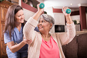 Caring, Latin descent home healthcare nurse conducts physical therapy exercises with African descent senior adult patient at home, assisted living, or nursing home setting.  She helps her with arm strengthening exercises using dumbbells.