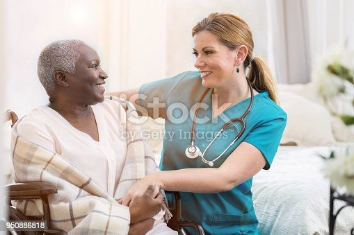 932074762istockphoto Home healthcare nurse smiles while checking on senior patient 950886818