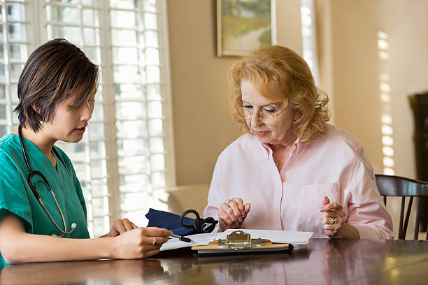 home healthcare nurse talking with a patient - question mark asking doctor nurse stock photos and pictures