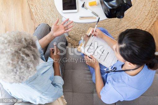 istock Home healthcare nurse talks with senior patient 1072676166