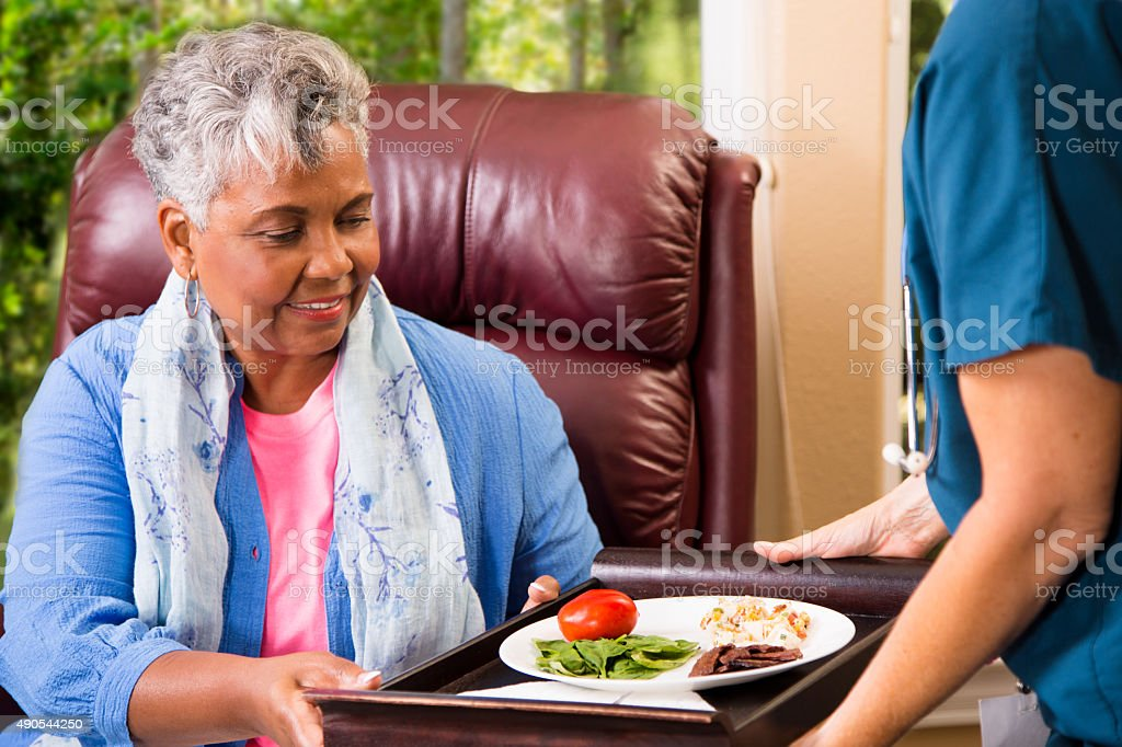 Home healthcare nurse with senior adult patient. Meal delivery. stock photo