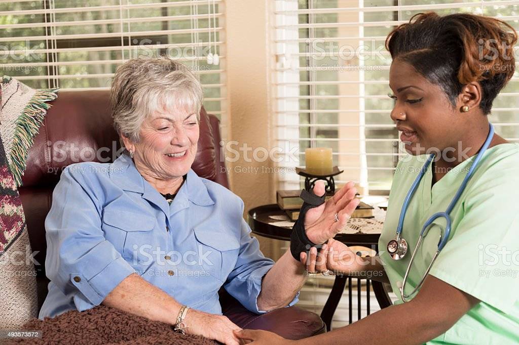 Caring home healthcare nurse conducts medical exam with senior adult...