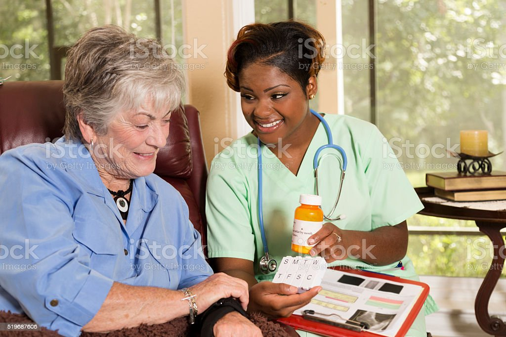Home healthcare nurse with senior adult patient. Medications. stock photo