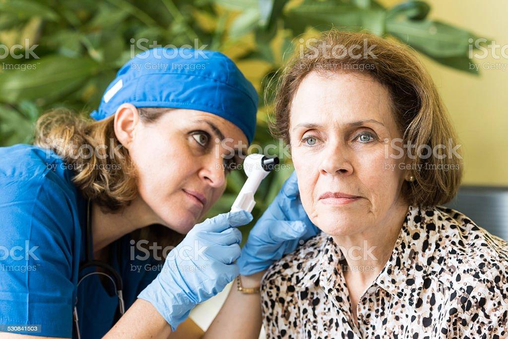 Home healthcare Doctor Examining Senior Female Patient's Ears 2015 Stock Photo