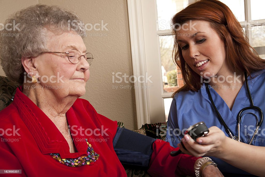 Home Healthcare Professional Showing Blood Pressure Reading to Patient royalty-free stock photo