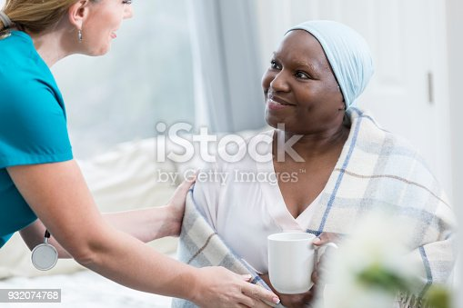 932074816istockphoto Home healthcare provider assists female cancer patient 932074768
