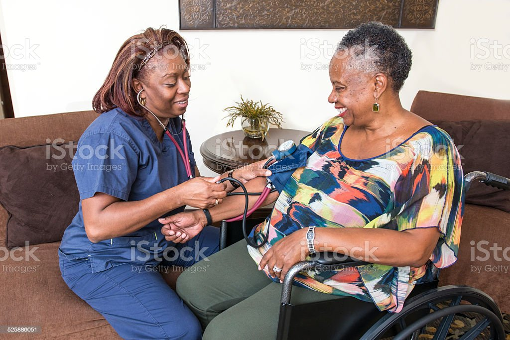 A home health care worker is taking a senior client\'s blood pressure.