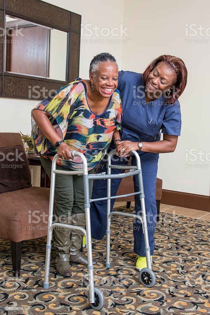 Home Healthcare Worker Assists Senior Woman stock photo