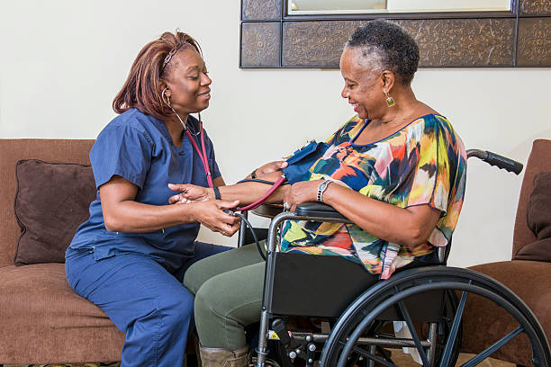 Home Healthcare Worker Assists Senior Woman A home healthcare worker is taking the blood pressure of a senior woman in a wheelchair. woman taking pulse stock pictures, royalty-free photos & images