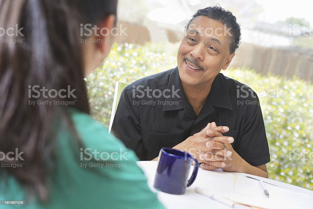 Home healthcare worker discussing care options with senior man royalty-free stock photo