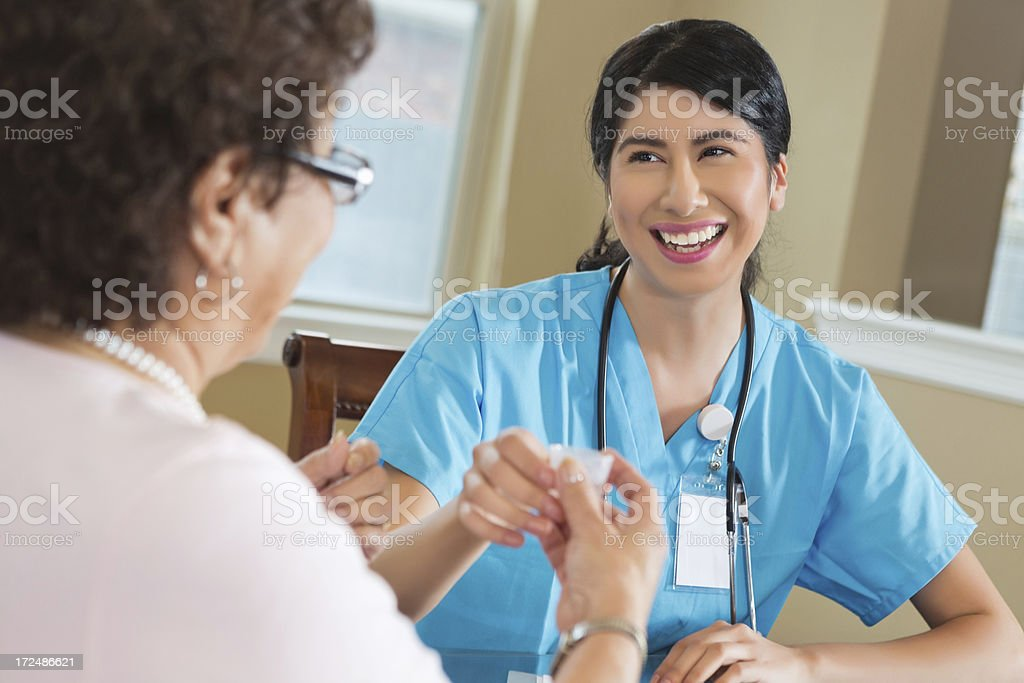 Home healthcare worker giving medication to senior patient royalty-free stock photo