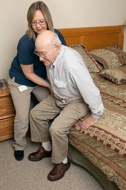 home healthcare worker using gait belt to assist patient - belt stock photos and pictures