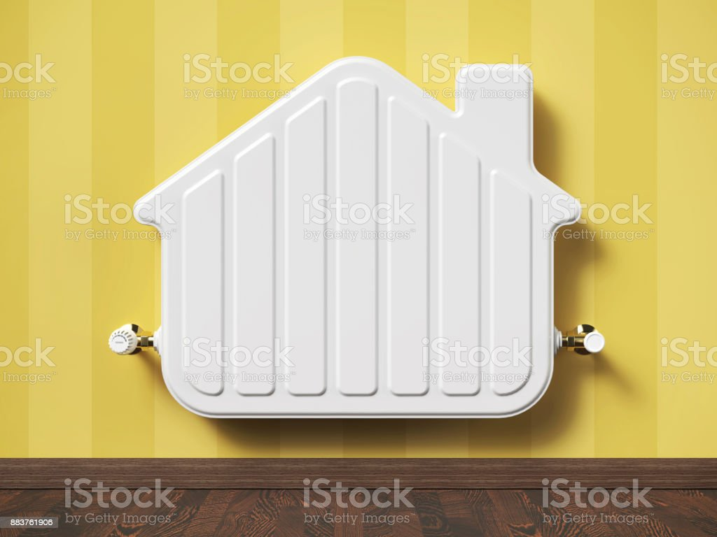 Home heater radiator in the shape house in living room. stock photo