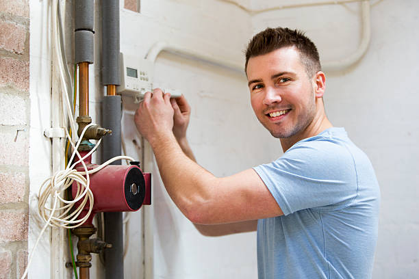 Home Heating Repairs A repairman fixes a heating system while he smiles at the camera. pipefitter stock pictures, royalty-free photos & images