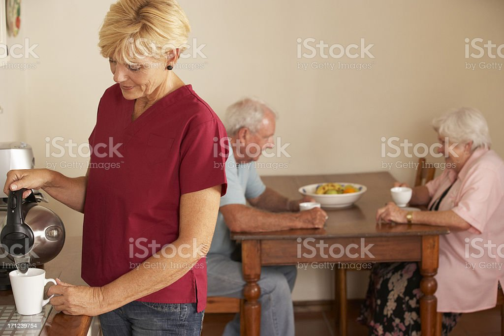 Home Help Sharing Cup Of Tea With Senior Couple royalty-free stock photo