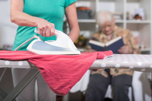 Home helper ironing clothes for an old woman stock photo
