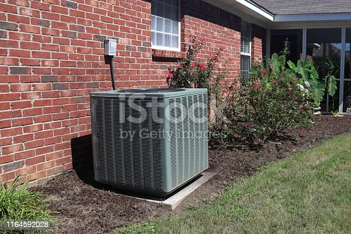 istock Home HVAC Unit next to modern brick home. 1164592028