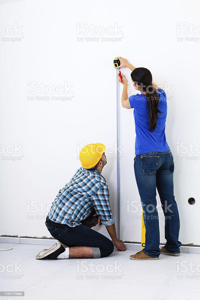 Home improvement - Couple measuring wall royalty-free stock photo