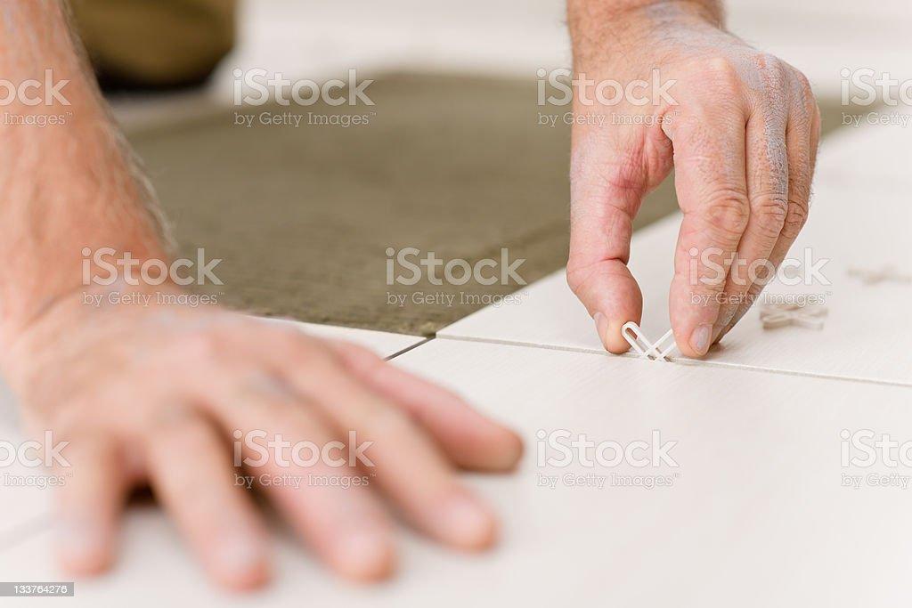 Home improvement - handyman placing tile spacer stock photo