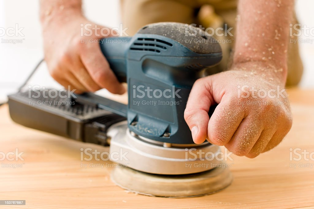 Home improvement - handyman sanding wooden floor stock photo