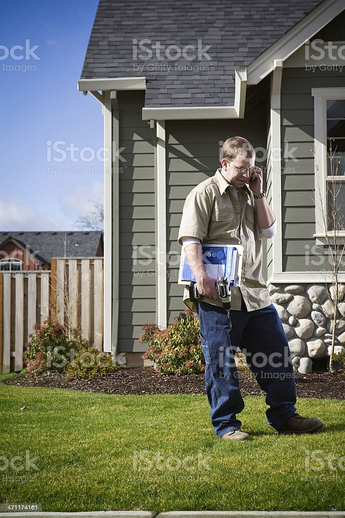 Home Improvement Man Outside of House on Cell Phone stock photo