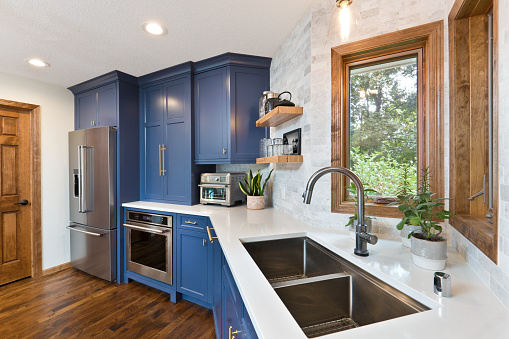 A contemporary kitchen renovation remodeling featuring a hardwood floor  kitchen sink, appliances and quartz counter top.