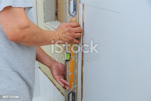 1138442636 istock photo Home improvement, renovation construction worker tiler is tiling, ceramic tile wall adhesive 955703286
