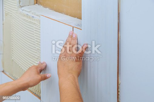 1138442636 istock photo Home improvement, renovation construction worker tiler is tiling, ceramic tile wall adhesive 955703320