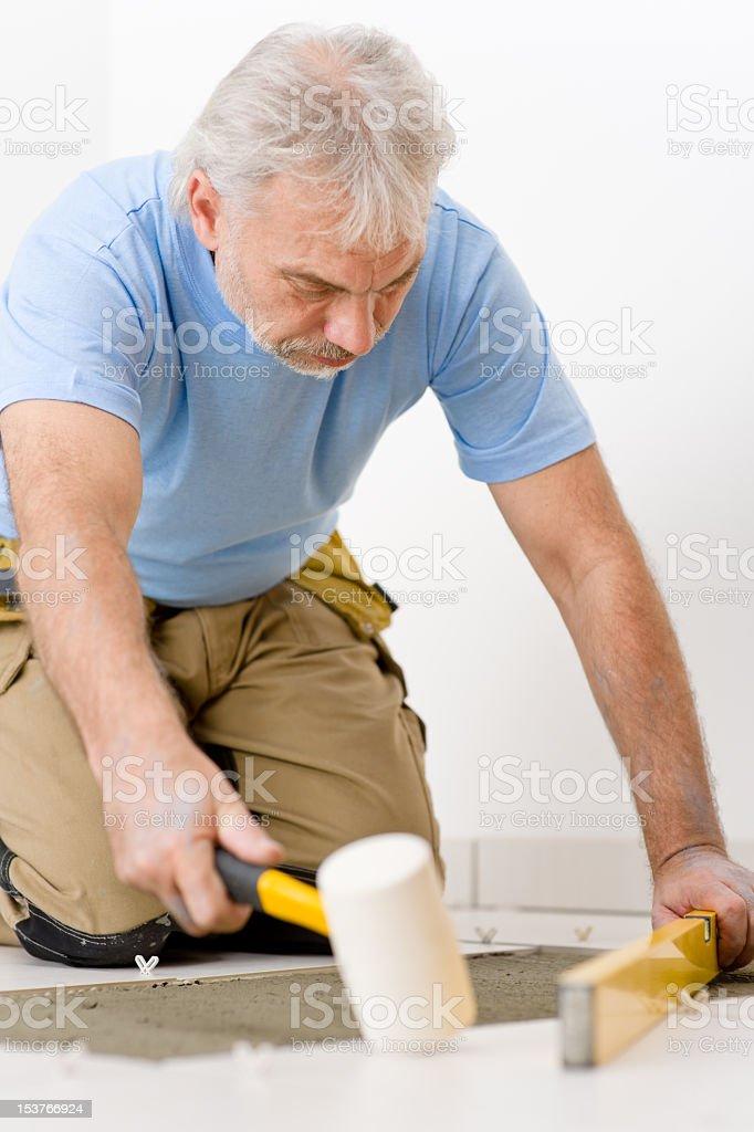Home improvement, renovation - handyman laying tile stock photo