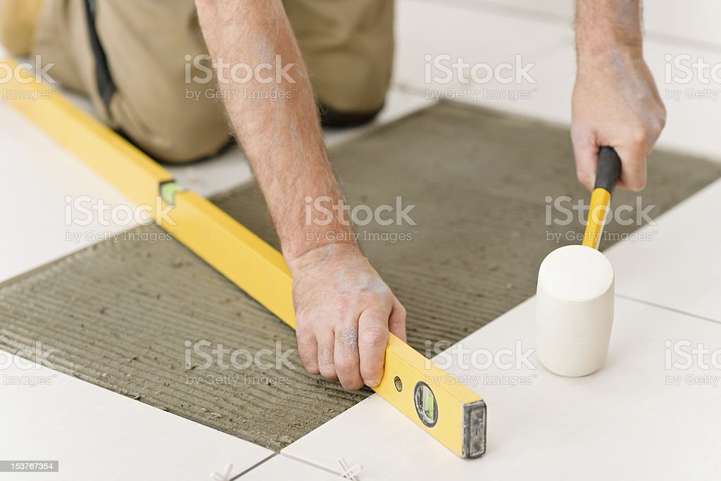Home improvement, renovation - handyman laying tile royalty-free stock photo