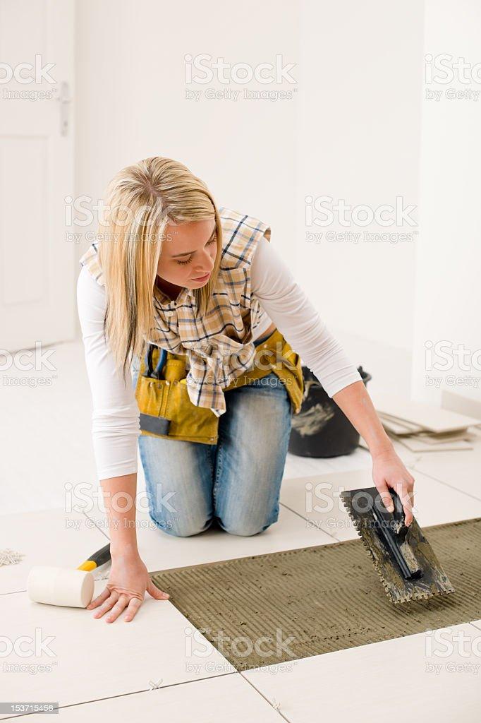 Home improvement, renovation - handywoman laying tile stock photo