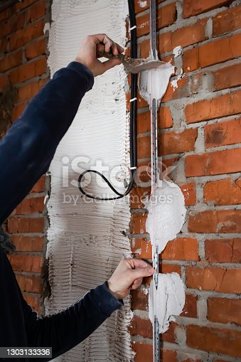 home improvement, the hands of the master install a metal guide for plastering a brick wall close-up