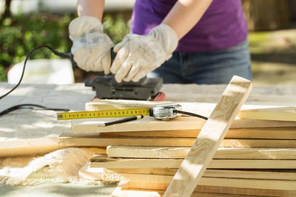 DIY - Home improvement; woman sanding wood plank stock photo