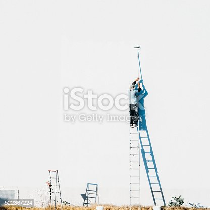 Hispanic man on top of a ladder painting a large facade on white with a paint roller.