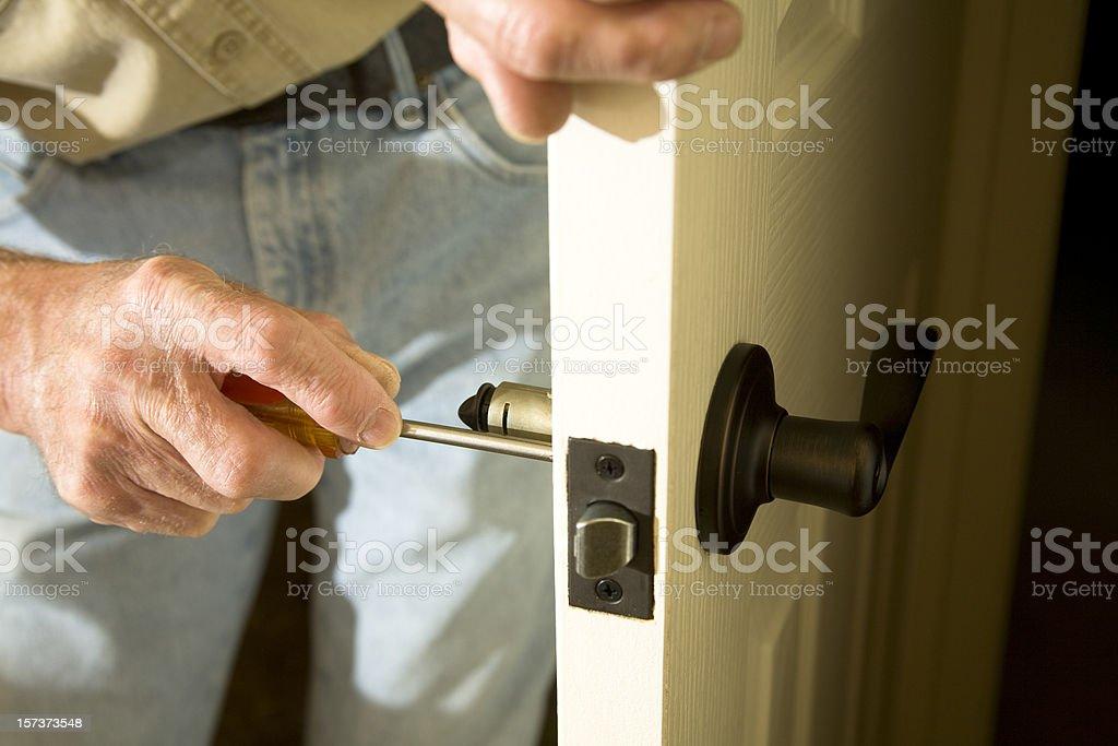 Home Improvements replacing door knob stock photo