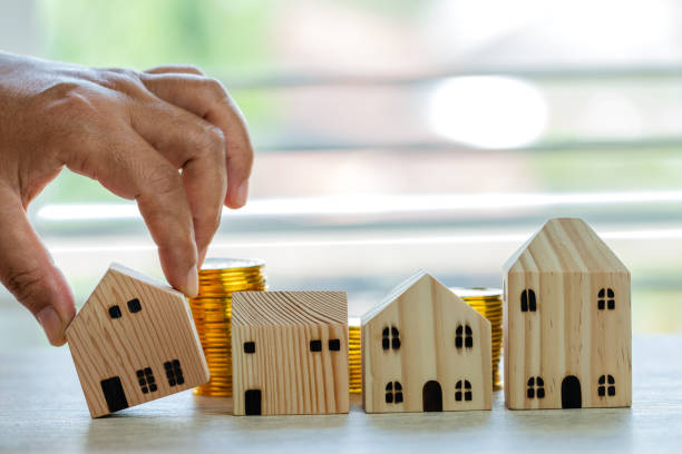 Home in business real estate investment or loan concept : Hands choose wooden home on dropshipping money coins placing on table office. Saving moneys for loan mortgage or buy new residential in life stock photo
