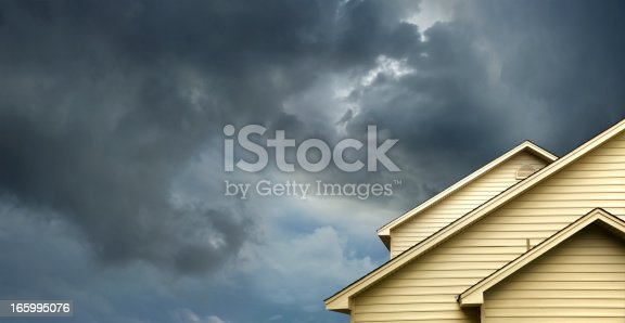 close up shot of yellow siding house over storm clouds.
